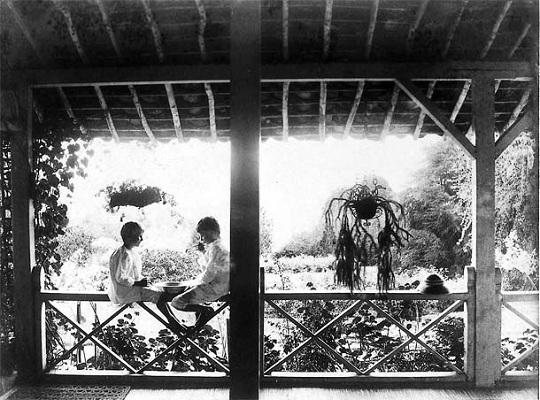 Edu (links) en Ru Kerkhoven, kinderen van Rudolf en Jenny, aan het bellen blazen op de balustrade van de voorgalerij van het administrateurshuis in Gamboeng, 1889.Foto: H. Udo de Haes. Copyright Stichting Indisch Thee- en Familiearchief Van der Hucht c.s.